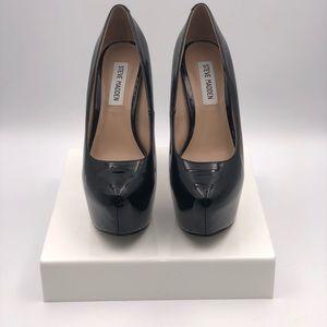 Patent, black platform high heeled pump.